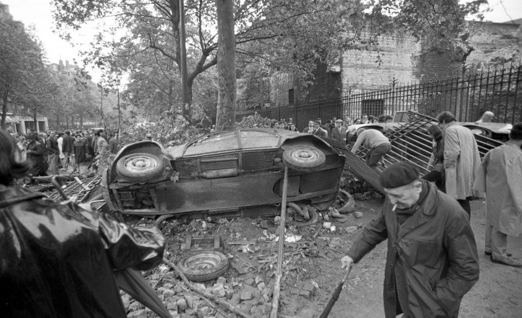 Barrikade aus einem seitlich umgekippten Auto und einem niedergerissenen Zaun sowie Pflastersteinen