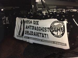 """Vermummte Demonstrierende mit einem Banner """"Hoch die antifaschistische Solidarität"""""""
