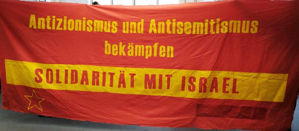 """Großes rotes Stofftransparent mit gelber Aufschrift """"Antizionismus und Antisemitismus bekämpfen - Solidarität mit Israel"""""""