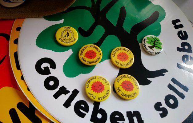 """sechs Buttons der Anti-AKW- und Ökologiebewgeung auf einem runden """"Gorleben soll leben""""-Aufkleber"""