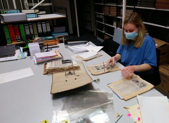 Praktikantin verpackt alte Unterlagen archivgerecht