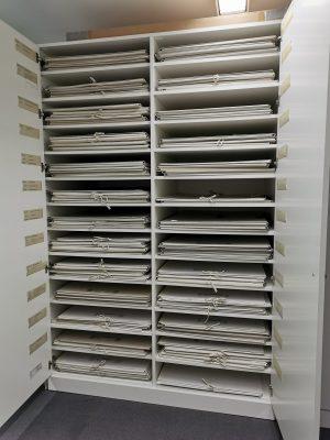 geöffneter Schrank, darin sind in Fächern liegend graue Plakatmappen zu sehen