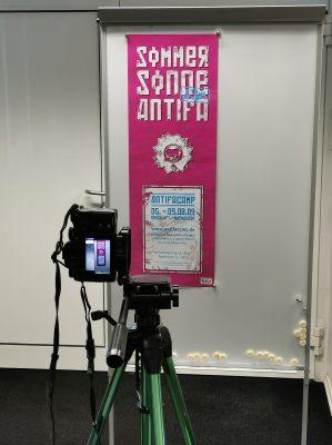 Plakat hänt an Magnetwand, davor auf Stative eine Digitalkamera, auf derem Display das Plakat klein zu sehen ist